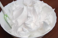 A Beautiful Rich and Creamy, White Whipped Meringue Cream in a large Mixing Plate Ready to Decorate A cake or Pie. Preparing Lemon royalty free stock photo