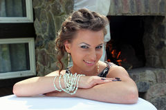 Beautiful rich girl. Portrait of a beautiful rich girl by the fireplace on the terrace Royalty Free Stock Photography
