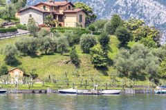 Italian rich house on the shore of lake Como, Italy. Beautiful rich house on the shore of lake Como surrounded with mountains, Italy Stock Photography