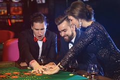 Beautiful and rich people playing roulette in the casino stock photos