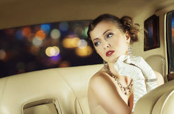 Beautiful and rich superstar girl sitting in a retro car. Young and beautiful celebrity woman sitting in a luxury retro car Stock Images