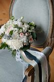 Beautiful rich wedding bouquet on a luxurious wooden chair, upholstered in fabric. Bouquet of pink and white roses and peonies, royalty free stock photography