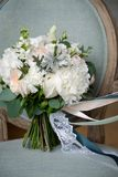 Beautiful rich wedding bouquet on a luxurious wooden chair, upholstered in fabric. Bouquet of pink and white roses and peonies, stock photos