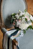 Beautiful rich wedding bouquet on a luxurious wooden chair, upholstered in fabric. Bouquet of pink and white roses and peonies, stock photo