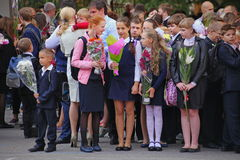 Beautiful, richly and solemnly dressed children with flowers at the school festival of knowledge. September 1, Knowledge Day in Russian school. Day of Knowledge Stock Image