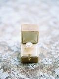 Beautiful ring on lace background. Beautiful ring with pearl on lace background Stock Images