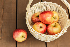 Beautiful and ripe apples in wattled basket Royalty Free Stock Photos
