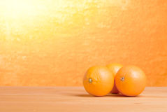 Beautiful ripe oranges on the table and a yellow orange backgrou. Beautiful ripe oranges  the table and yellow orange background Stock Photos