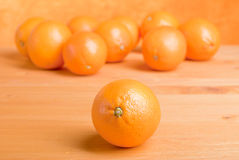 Beautiful ripe oranges on the table and a yellow orange backgrou. Beautiful ripe oranges on the table and yellow orange background Royalty Free Stock Images