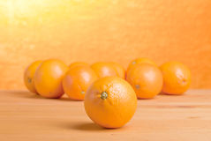 Beautiful ripe oranges on the table and a yellow orange backgrou. Beautiful ripe oranges on the table and yellow orange background Stock Image