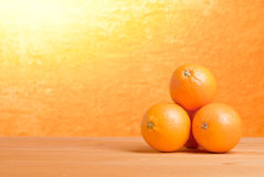 Beautiful ripe oranges on the table and a yellow orange backgrou. Beautiful ripe oranges on table and yellow orange background Stock Photos