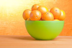 Beautiful ripe oranges on the table and a yellow orange backgrou. Nd Royalty Free Stock Image