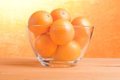 Beautiful ripe oranges on the table and a yellow orange backgrou Stock Images