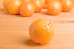 Beautiful ripe oranges on the table and a yellow orange backgrou Royalty Free Stock Photos