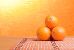 Beautiful ripe oranges on the table and a yellow orange backgrou. Beautiful ripe oranges on the table and yellow orange background Stock Photos