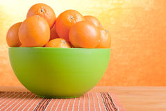 Beautiful ripe oranges on the table and a yellow orange backgrou Royalty Free Stock Photography