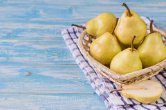 Beautiful ripe pears on a blue wooden table. Ripe pears in a basket on a rustic wooden table. The concept of healthy eating with natural products Stock Image