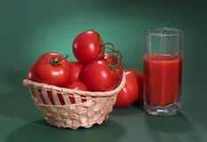 Beautiful ripe tomatoes on a green background. Tomato juice royalty free stock photo