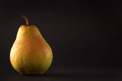 Beautiful ripe yellow pear on black background Royalty Free Stock Images