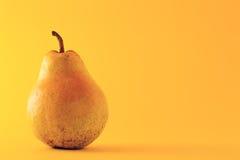 Beautiful ripe yellow pear on yellow background Stock Photo