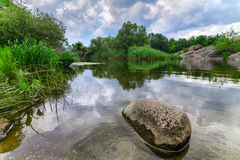 Beautiful river boulder with sky stormy clouds,  moving water Royalty Free Stock Photos