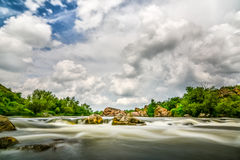Beautiful river flow with sky stormy clouds,  moving water - lon Royalty Free Stock Images
