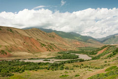Beautiful river flows in the green valley at the Central Asian mountains covered with white clouds. Bright day in beautiful rural Kyrgyzstan country Stock Photo