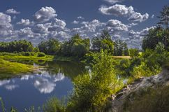 Beautiful river in green forest. Landscape with cloudy sky.  royalty free stock photo