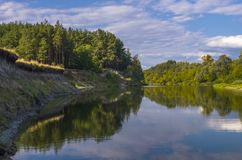 Beautiful river in green forest. Landscape with cloudy sky.  stock photos
