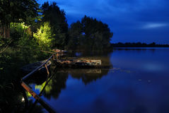Beautiful river landscape. Beautiful green and blue night river landscape with boats and pipe Royalty Free Stock Photography