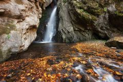 Beautiful river waterfall in autumn forest, a small waterfall part of Fotinski Waterfalls, Rhodope Mountains, Bulgaria Royalty Free Stock Image