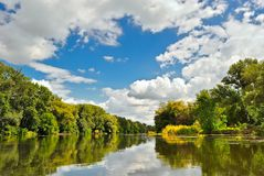 Beautiful river with wooded banks. Under blue cloudy sky Royalty Free Stock Photos