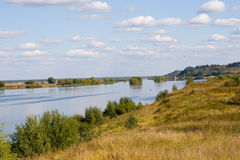 Beautiful river and yellow meadow. Under the summer sky Stock Photos