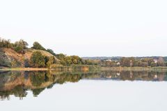 Beautiful riverfront scenery of calm water and part of forest Stock Photography