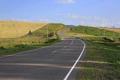 Beautiful road among farm fields Stock Photo