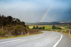 Beautiful road with rainbow in blue sky, South Island, New Zealand Stock Photography