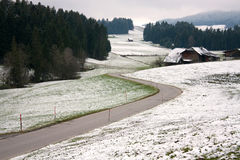 Beautiful roads between snow and green grass in early winter time Royalty Free Stock Photos