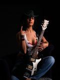 Beautiful rock chick. Beautiful latino rock chick with an electric guitar giving the devilhorns sign with her hand Royalty Free Stock Image