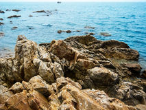 Beautiful rock and lonely small ship on the sea Royalty Free Stock Image