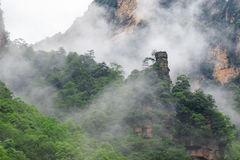 Beautiful Rock Mountains with Green Trees Surrounded by White Mist Clouds. Green Mountain Landscape Royalty Free Stock Photos