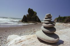 Rocks stacked on top of each other on a beach stock image