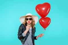 Beautiful rocker girl in leather jacket and summer hat kissing heart shaped lollipop and holding heart shaped balloons. royalty free stock photo