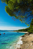 Beautiful rocky beach  in Croatia with a view on Zlatni Rat or Golden Cape beach Royalty Free Stock Image