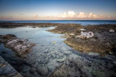 Beautiful rocky beach at dusk and sea waves stock photo