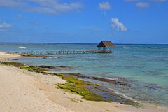 Beautiful rocky beach with wooden jetty pier hut and a white boat Royalty Free Stock Photos