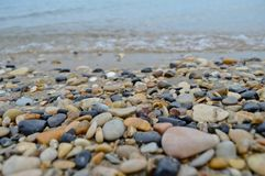 The beautiful rocky coast of Corfu. A close-up macro picture of Corfu beach with small rocks and waves, with the horizon in the background Royalty Free Stock Image
