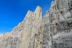 Beautiful rocky mountain wall Dolomiti di Brenta, Italy. Beautiful rocky mountains in summer with blue sky. Beautiful rocky peaks, mountain and gray stones stock photography