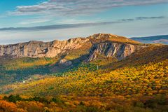 Beautiful rocky mountains and a view of the autumn forest at the foot. Beautiful scenery stock image