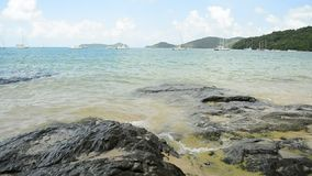 Beautiful rocky and sandy beach with clear water under cloudy blue sky, Low angle view on Ao Yon Bay in the andaman sea. Beautiful rocky and sandy beach with stock footage