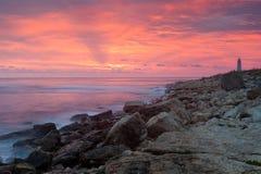 Beautiful rocky sea beach with lighthouse Stock Photo